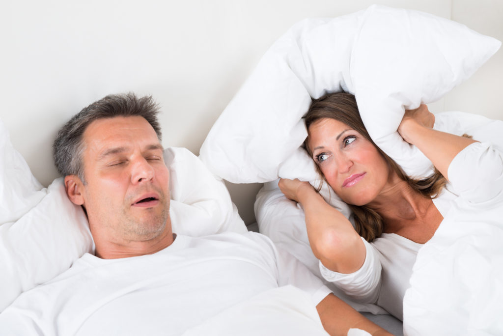 Woman covering her ears with pillow while man is snoring from sleep apnea symptoms.