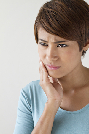 Young woman holds the side of her face with a tooth ache and thinking about seeing an emergency dentist in Pleasanton, CA.